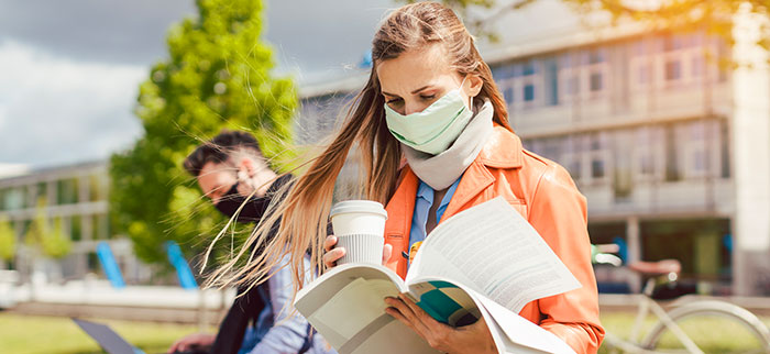 Male and female college students wearing face masks on campus