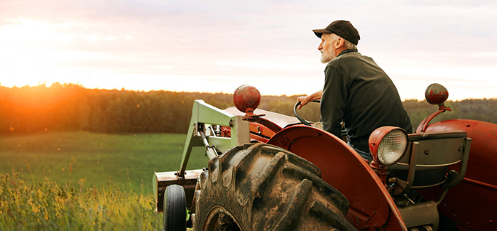 Image of an older farmer on a tractor looking at his farm