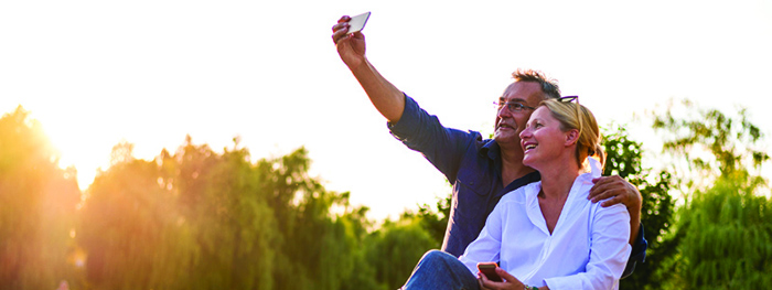 Man and woman taking a selfie at a park. Elements of financial well-being: present and future security and freedom of choice.