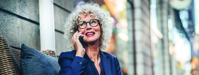 Female Social Security recipient on a business call. Full retirement age based on birth year: 1943–1954 is 66, 1955 is 66 and 2 months, 1956 is 66 and 4 months, 1957 is 66 and 6 months, 1958 is 66 and 8 months, 1959 is 66 and 10 months, and 1960 and later is 67