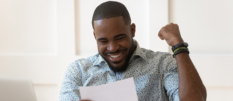 African American man happily looking at a refund from his auto insurance carrier.