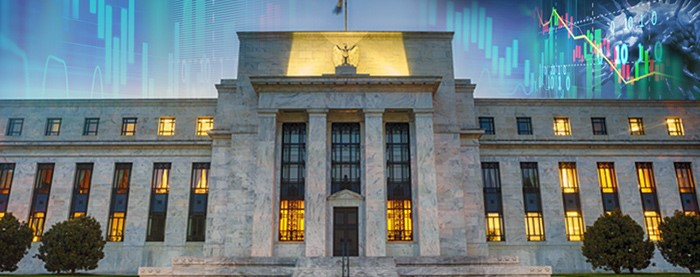An image of the Federal Reserve Building with stock market ticks in the sky.