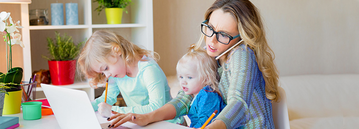 Busy mom working from home with toddler in her lap and grade-school-age daughter beside her.