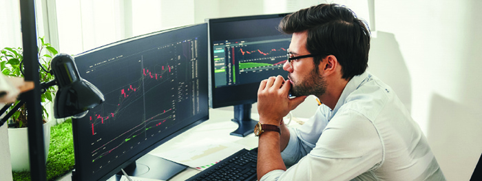 Man tracking financial developments on two computer monitors.