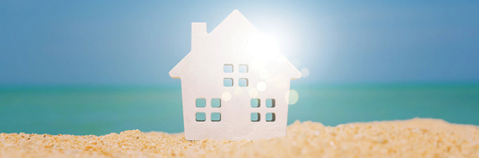 White poster board house on a beach background.