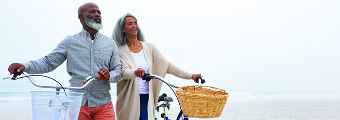 Man and woman walking their bikes along a beach.