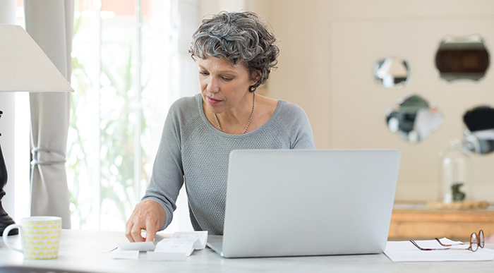 IMAGE of grey haired woman at her laptop looking at paperwork
