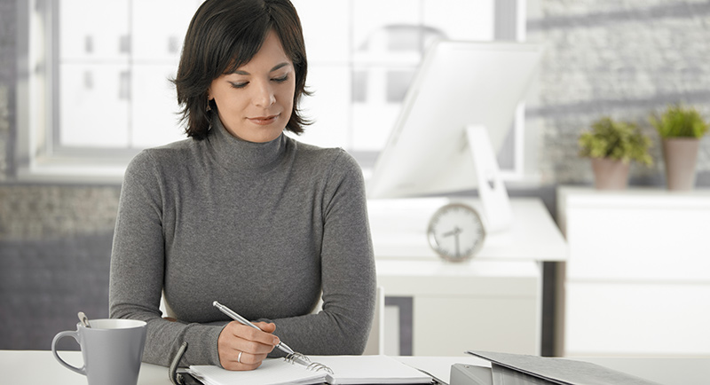 Image of a woman at her desk reviewing her inventory.