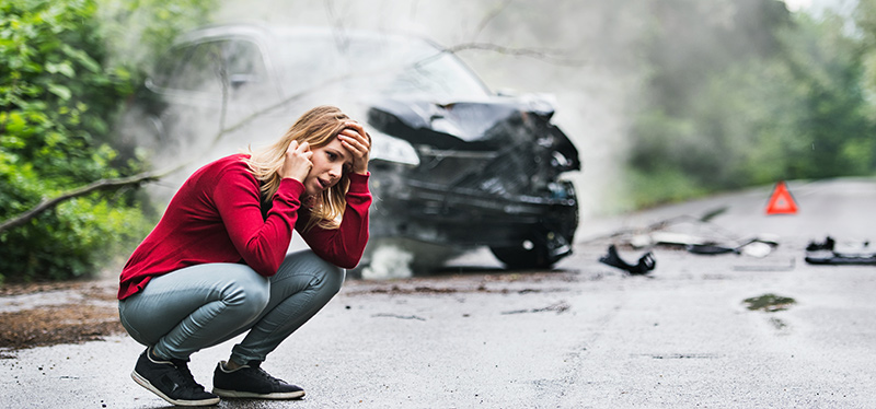 IMAGE of a woman talking on the phone near a car that was in an accident.